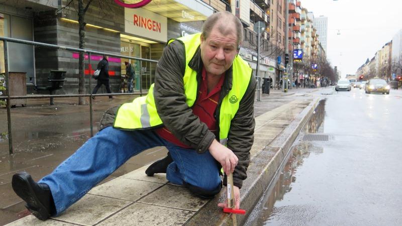Per Ola Johansson är en av de som haft praktikplats hos landstinget. Iklädd varningsväst och sitttandes på huk mäter han en trottoarkant.