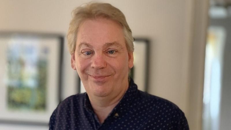 En man i blont hår och med buskiga ögonbryn och blicken mot kameran, iklädd en mörk skjorta med ljusa prickar.
