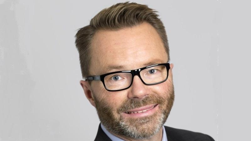 Peter Carpelan har brunt hår, gråsprängt kort skägg och svarta glasögon.