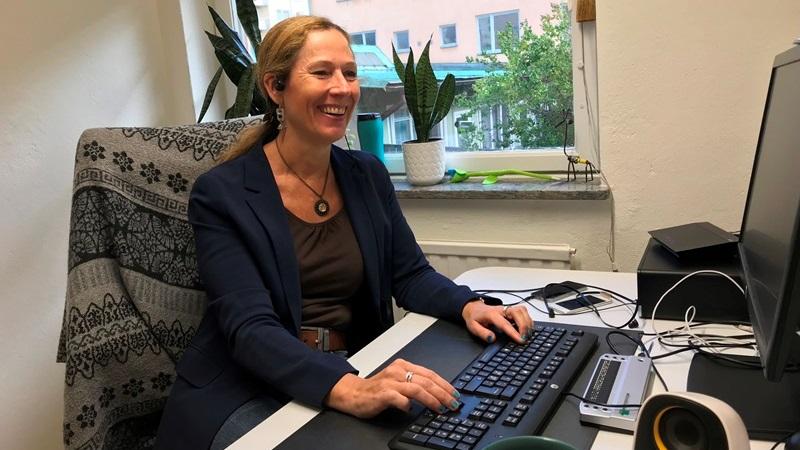 Kvinna i halvbild, sitter vid skrivbord och skriver på en dator. Hon har rågblont långt hår i tofs. Mörkblå kavar med kakigrön topp under. Hon skrattar.