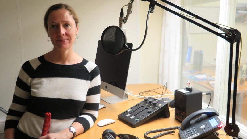 En kvinna med håret i tofs och svart-vit-randig tröja håller i sin käpp, lutad mot ett ståbord i ljudstudiomiljö med mikrofoner.