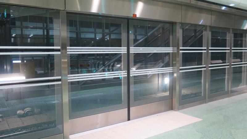 Bild på plattformsbarriärer vid perrongkanten, en vägg av glas med vita horistontala streckmarkeringar.