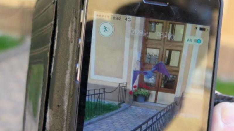 Bild på mobiltelefonskärm där en tcknad blå figur flyger framför en dörr.