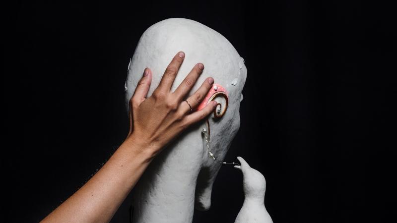 Hand på vit skulptur av huvud.