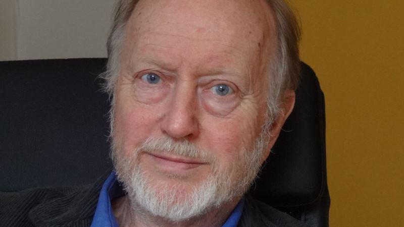 Närbild på professor Jerker Hetta som är tunnhårig, har grått skägg och blå ögon.