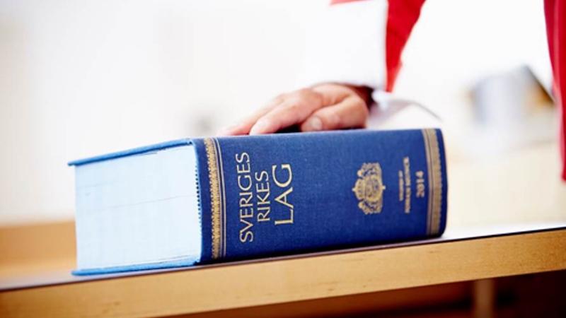 Svensk lagbok i blått ligger på ett bord, en hand vilar på boken