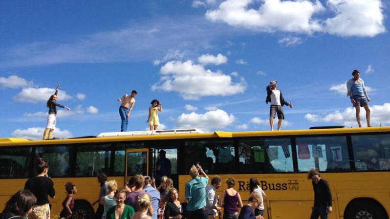 En gul buss med männiksor både utanför och på taket.