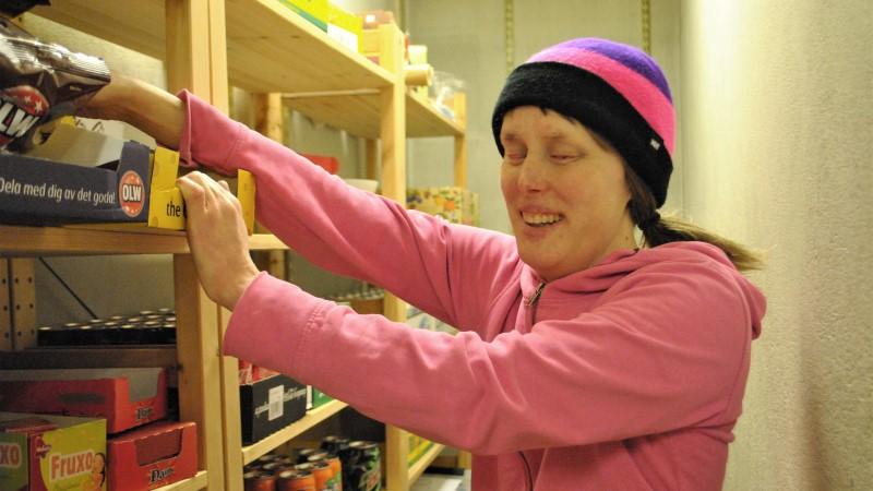 Kvinna i rosa letar bland hyllor i ett stort skafferi.