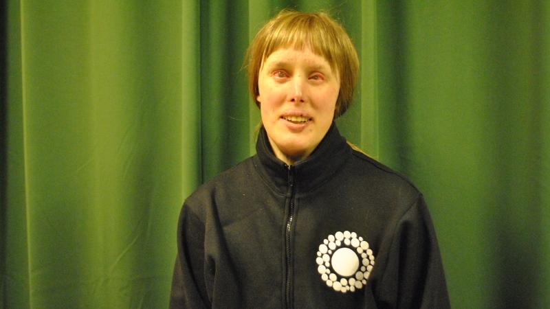 Kvinna i sportjacka, blont hår och lugg.