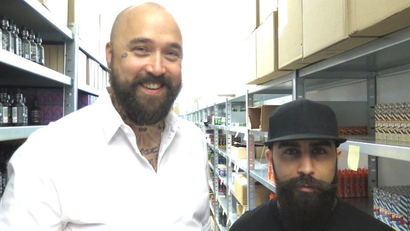Två leende män med mörka helskägg, en längre med kal hjässa och en kortare med keps.