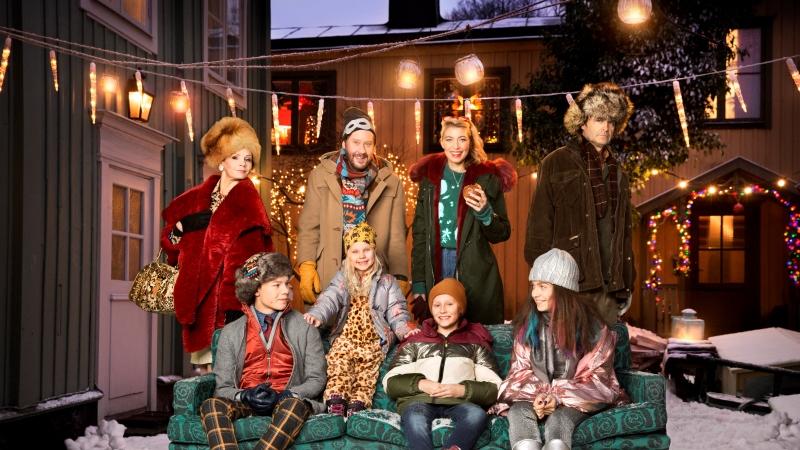 Skådespelarna från SVT:s julkalender samlade i och bakom en soffa på en julbelyst innergård.