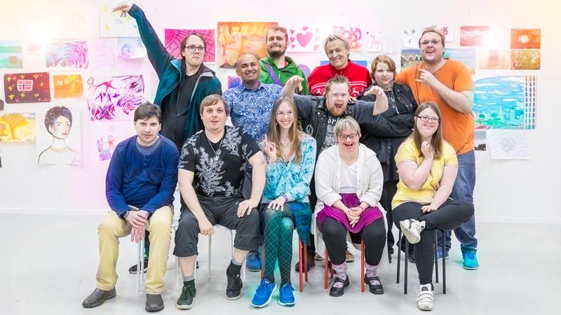 Lars Lerin och Junior med tio av deltagarna som medverkar i Lerins lärlingar. Alla skrattar och är samlade framför en vägg med färgglada målningar. Foto Ulrika Malm SVT legal