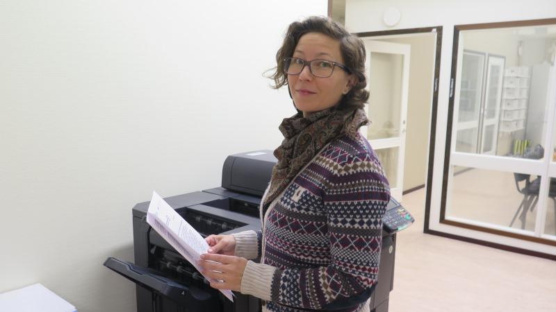 Kvinna med kort mörkt, vågigt hår och glasögon. Hon småler, är klädd i sjal och möstrad tjocktröja och står vid en kopieringsapparat med några papper i handen.
