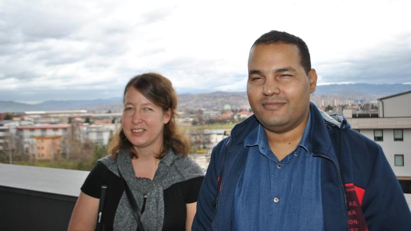 En man och kvinna med mörkt hår, står med ryggen mot broräcke, stad i bakgrund, molnig himmel