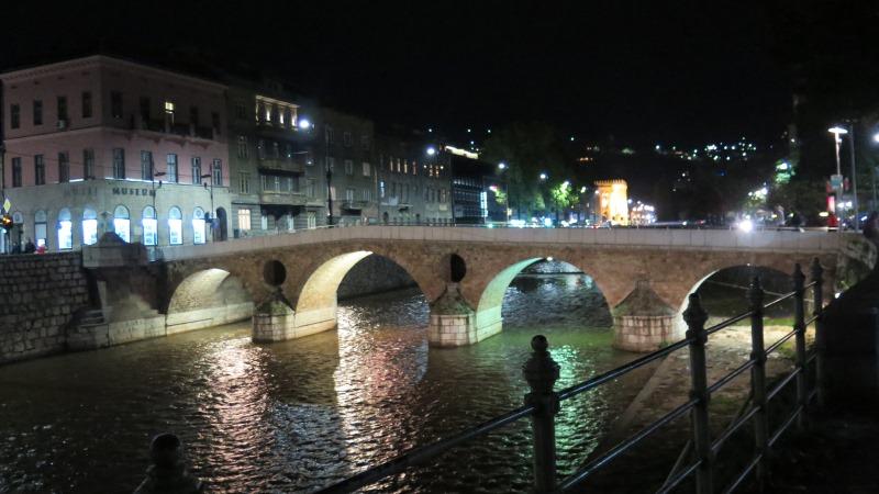 Den latinska bron mitt i Sarajeo. En smal bro med murade valv. På andra sidan floden fyravåningshus i sten från förra sekelskiftet. Det är natt, men bron och husens fasader är upplysta.