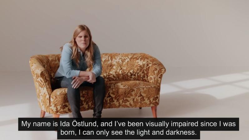 En kvinna som sitter på en soffa i ett vitt rum utan andra möbler.