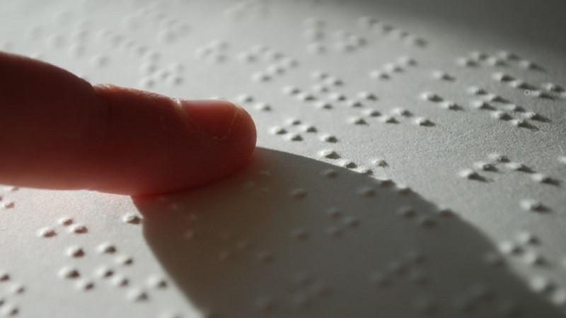 Ett pekfinger som dras över ett ark med punktskrift och kastar en stor skugga. Foto: Stefan Malmesjö/Flickr