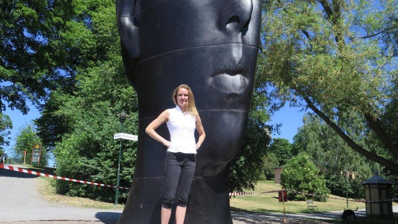 En blond sommarklädd kvinna står framför en enorm svart skulptur i form av ett flickansikte.