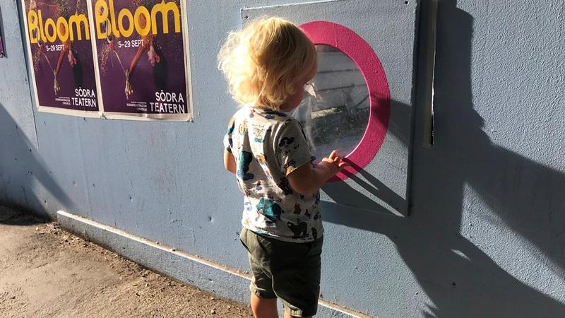 En två-årig blond pojke, står vid ett blått plank och tittar ner på en byggarbetsplats genom ett runt litet fönster. Han har på sig en grå T-shirt med figurer på, och kakigröna kortbyxor.