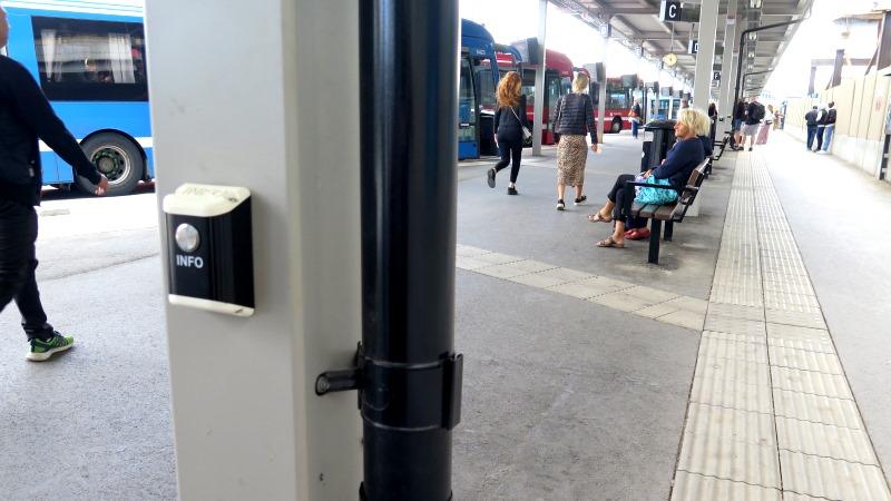 Bussterminalen vid Slussen med väntande resenärer. I förgrunden en info-knapp på en stolpe, bussar på rad skymtas i bakrgrunden.