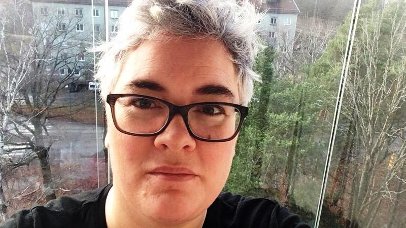 Närbild på kvinna med kort grått hår och glasögon. Sitter framför ett fönster med grön utsikt.