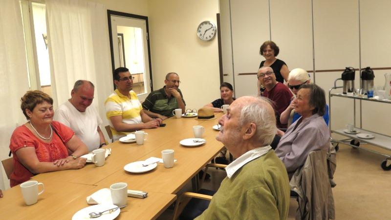 Ett tiotal leende personer sitter vid ett bord fyllt av kaffekoppar och fat.