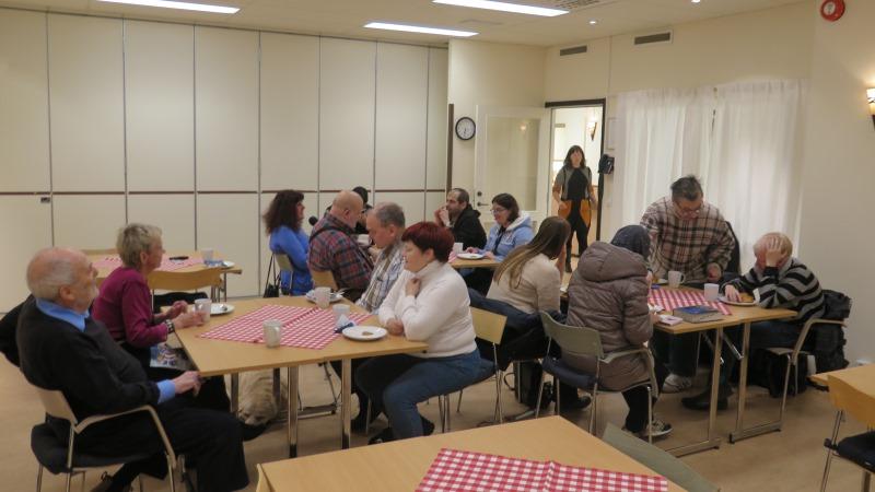 Ett dussintal personer i olika åldrar sitter vid bord och fikar