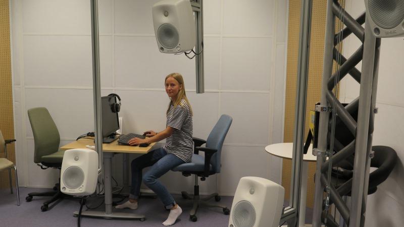 Kvinna med långt blont hår och randig tröja sitter vid en dator i en ljudstudio med flera små högtalare som hänger på ställningar.