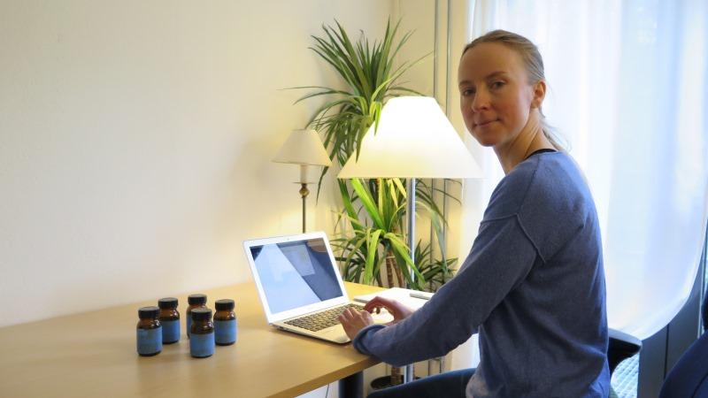 Blond kvinna med långt hår i tofs sitter framför en dator klädd i blå tröja. På skrivbordet står också mörka glasburkar och i bakgrunden en grön växt.