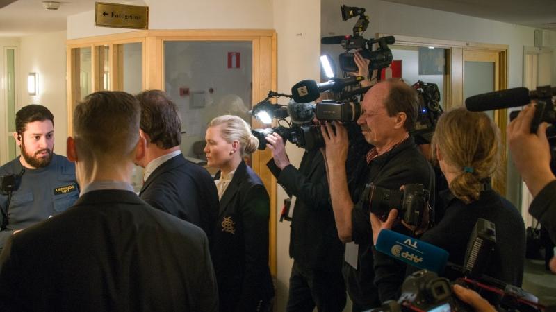 Vid ingången till säkerhetssalen står en vakt framför en hord av journalister med tv-kameror med strålkastare och framsträckta mikrofoner.