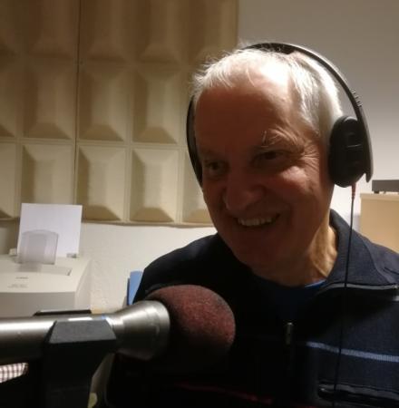 Äldre man med brett leende och vitt hår med lurar på huvudet i en radiostudio.