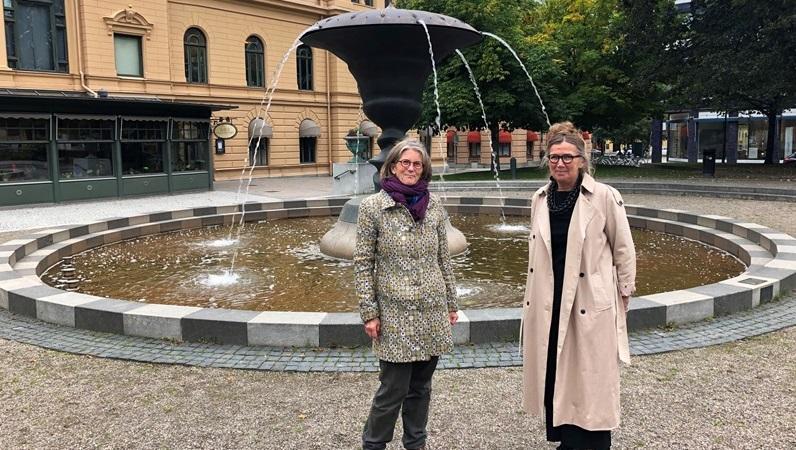 Två leende kvinnor står framför en hög, fontänskulptur i en stadspark.Kvinnorna är i övre medelåldern. Den ena har grått hår i p