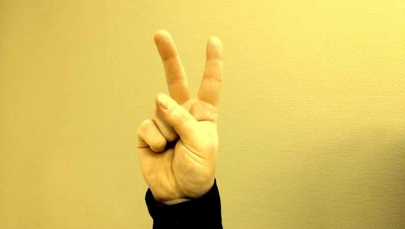 En hand, fingrarna gör V-tecken. Pek och långfinger hålls upp som i ett V