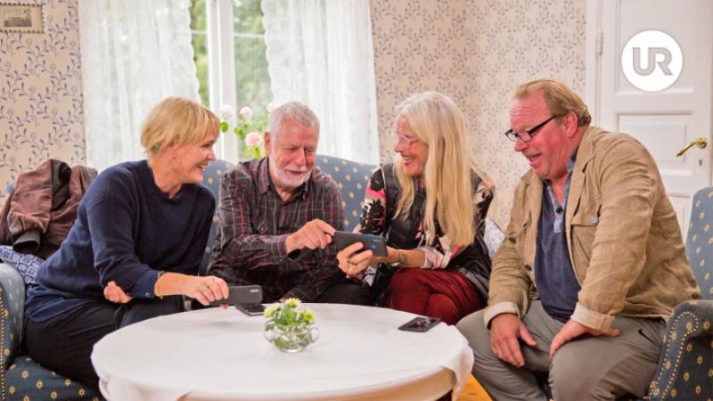 Fyra äldre personer sitter i en soffa runt ett bord, två kvinnor och två män.