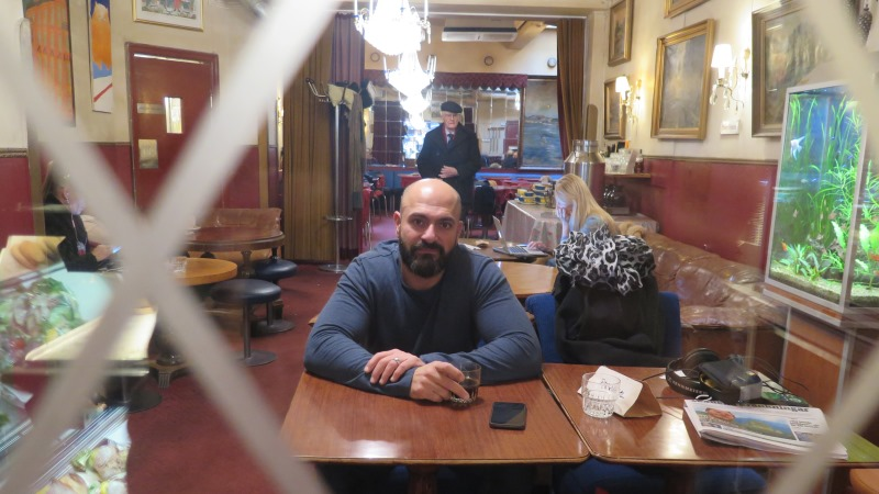 Foto taget genom en delvis frostad glasruta. En man utan hår med mörkt helskägg sitter vid ett kafébord. Kristallkronor och tavlor med guldram i bakgrunden och ett akvarium skymtar till höger.