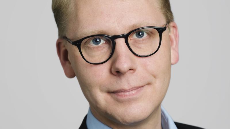 Blond man med glasögon som har svarta bågar.