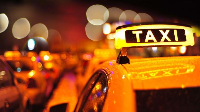 Närbild tak på en gul taxi med taxiskylt. Åker i stad, natt.