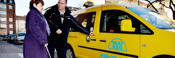 Färdtjänstförare i färd med att öppna framdörren för kvinna med vit käpp.