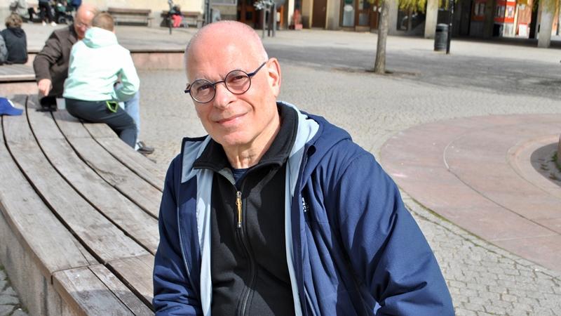 Leende äldre man med glasögon och blå sportjacka, sitter på en bänk