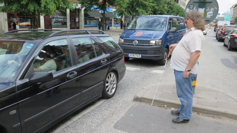 Håkan Thomsson står med sin käpp vid övergångställe nära passerande bilar
