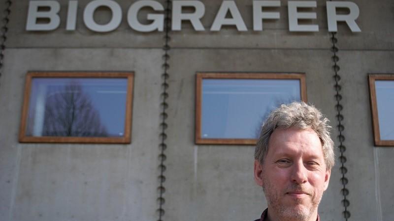 En småleende man med kort gråsprängt rufsigt hår i nedre delen av bilden. Han står framför Filmhusets grå fasad, i övre kant skymtar stora bokstäver som bildar ordet biografer.