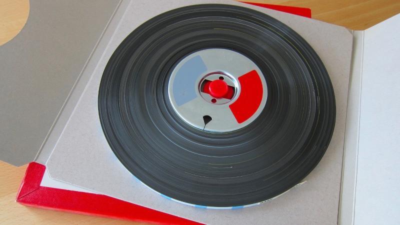 Ett svart ljudrullband ligger i en kartong