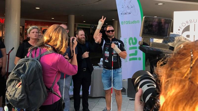 En man med solglasögon klädd i sporttröja med reklamdekaler och jeansshorts håller i en mikrofon och gör fredstecknet med två fingrar i luften. Till vänster en svartklädd tolk, i förgrunden ryggtavlor av fotografer.