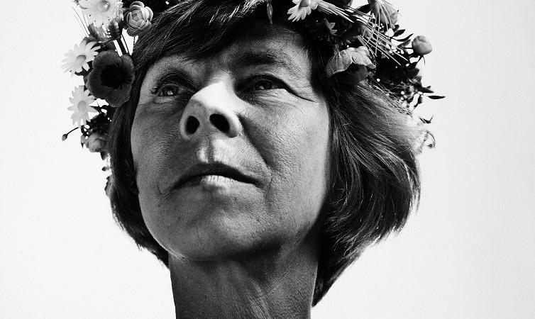 Ett svart-vitt foto av Tove Jansson. Hon har kort hår och en blomkrans runt huvudet.