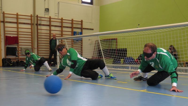 Tre goalballspelare beredda framför mål när bollen kommer