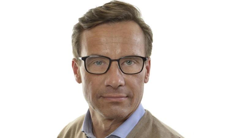 Porträtt på moderaten Ulf Kristersson. Han har ljusbrunt hår, gröna ögon bakom glasögon med mörka bågar och är klädd i ljusblå skjorta under beige tröja.