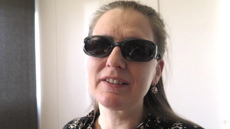 Kvinna med långt mörkblont hår och mörka glasögon.