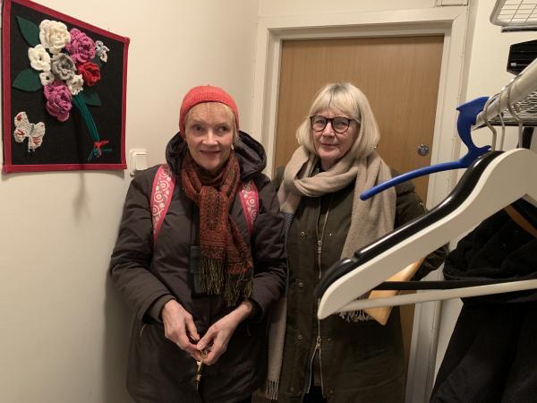 Två kvinnor står med ytterkläder på i en hall. Aini Hjerpe till vänster bär en rosa mössa. Margareta Frank Östergren till höger har blont hår och en beige halsduk.