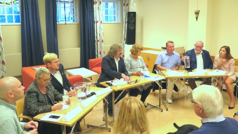 Landstingspolitiker på rad vid ett halvcirkelformat bord. I mitten moderatorn Håkan Thomson och distriktets ordförande Karin Hjalmarson.
