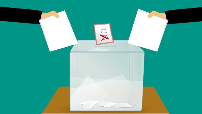 Tecknad bild med en stor låda med valsedlar i. Två händer som håller i valsedlar sträcks fram mot lådans öppning.